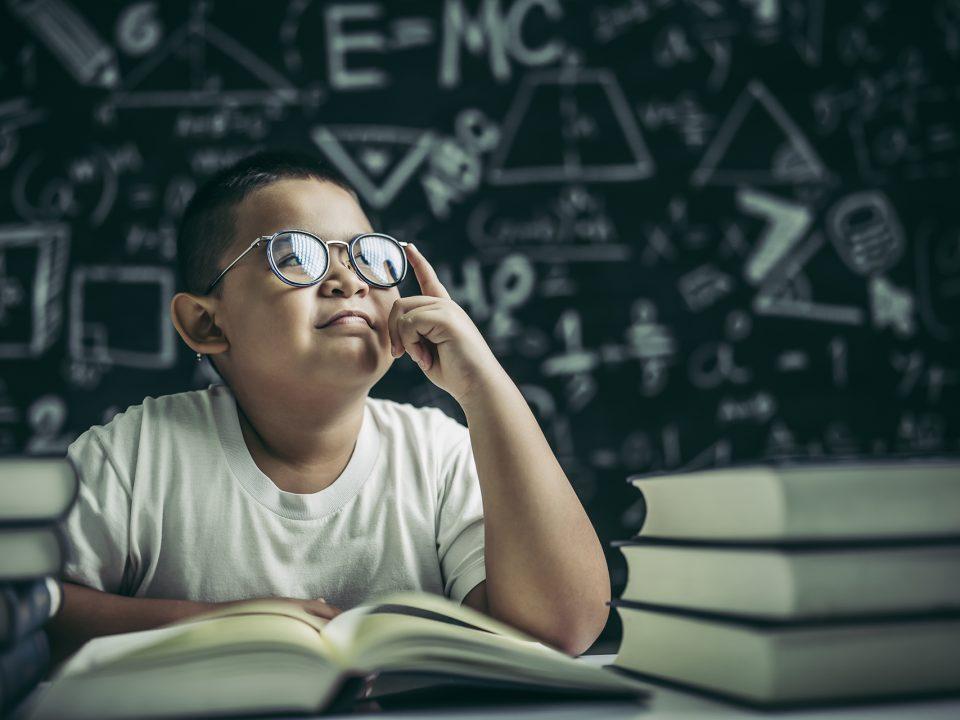 Bambino con occhiali che studia